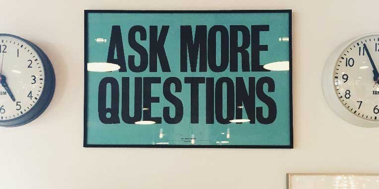Office wall with sign saying ask more questions
